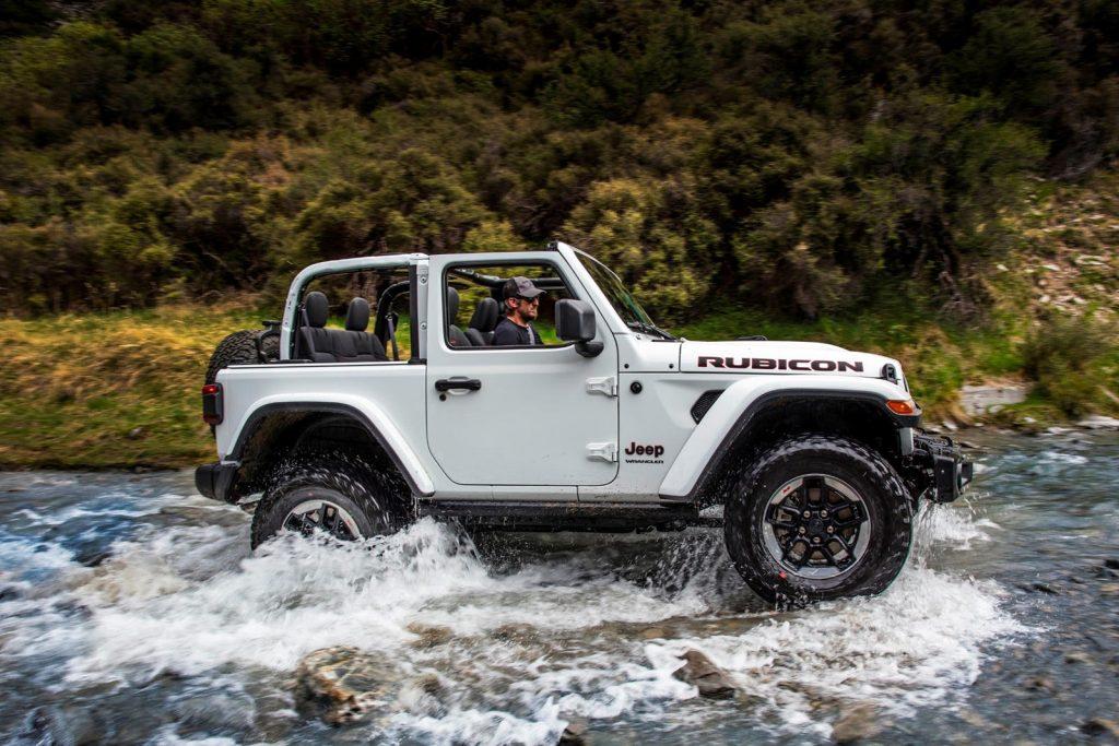A Jeep Wrangler Rubicon riding in a creek.