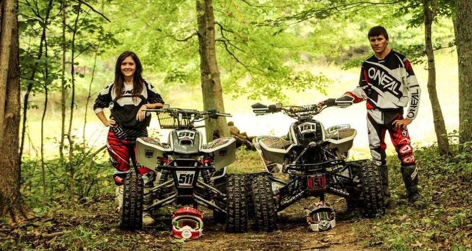 Kristen and her husband pose in the woods with their quads.