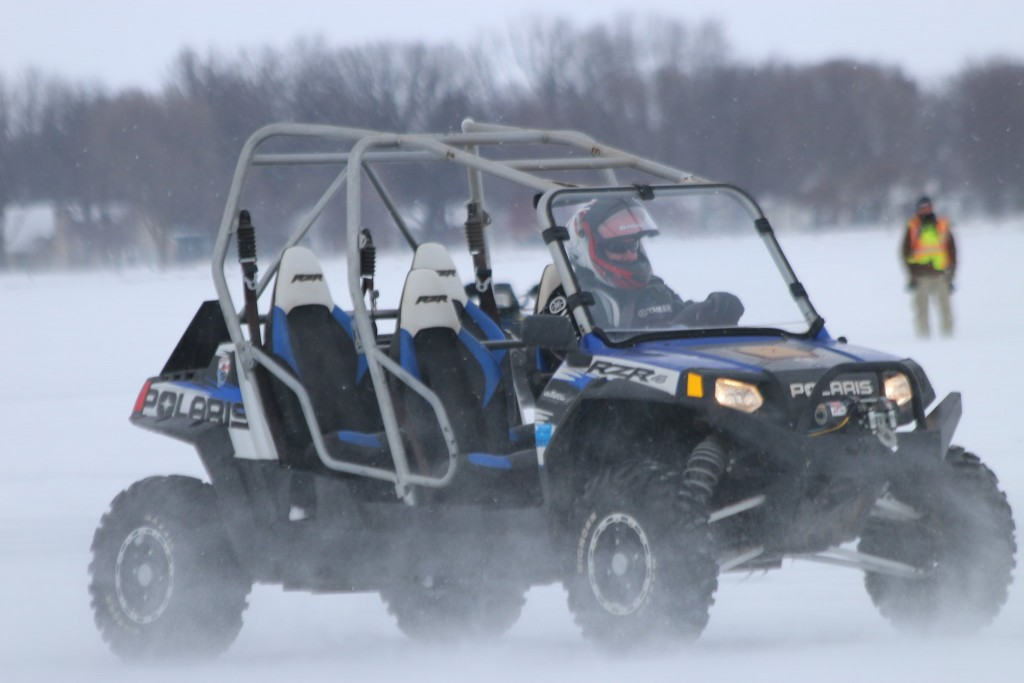 This 4 seater RZR is cruising on a frozen lake.