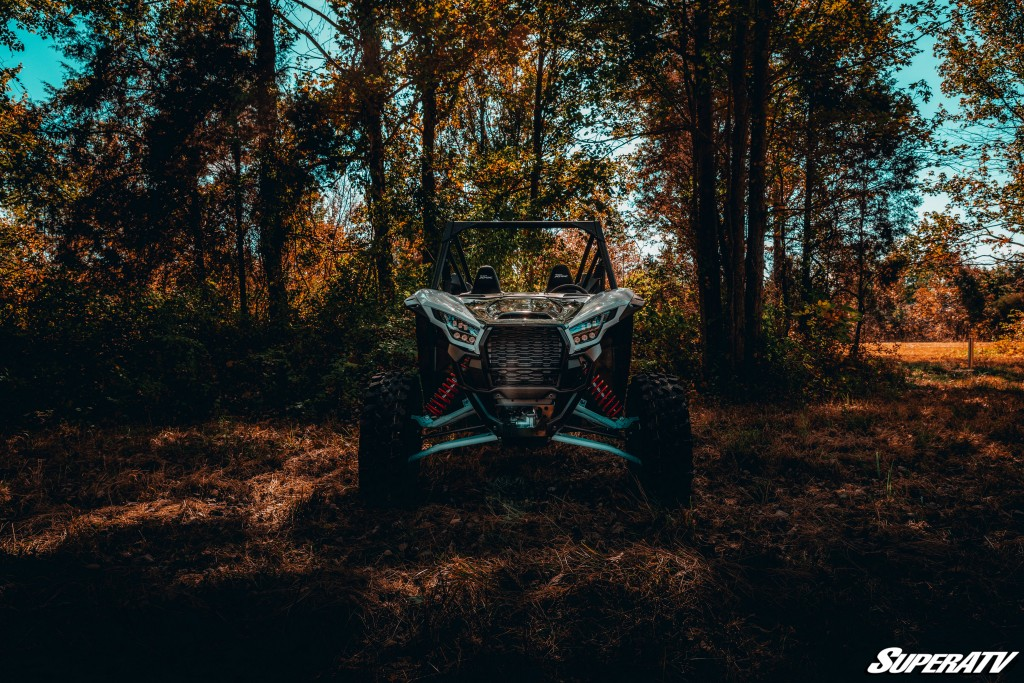 This head-on photo shows the Kawasaki Teryx KRX 1000 parked in a grove of trees. The impressive suspension of this machine is evident.