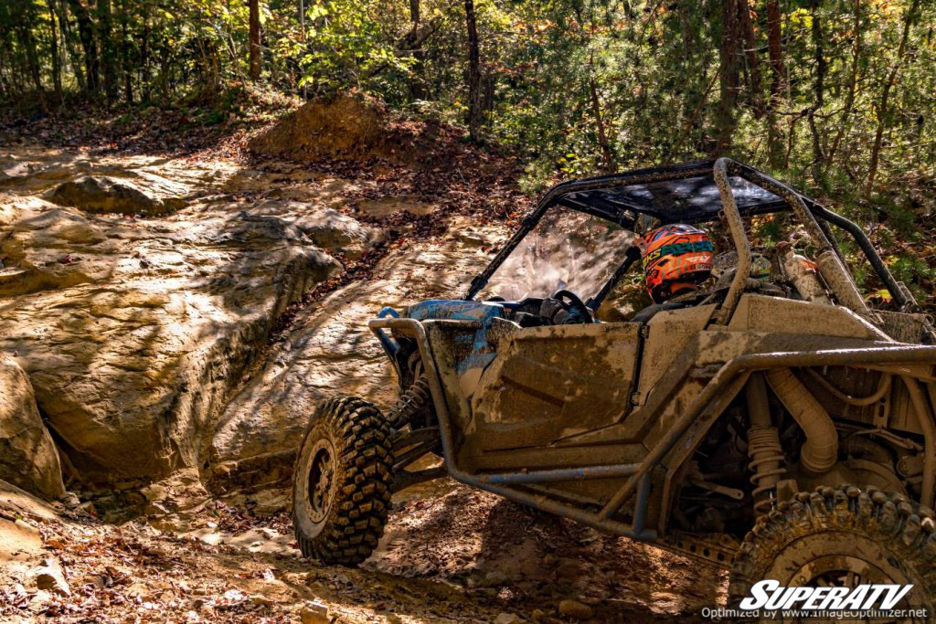 This photo shows a machine making its way through a muddy trail using a set of SuperATV's Warrior Tires.