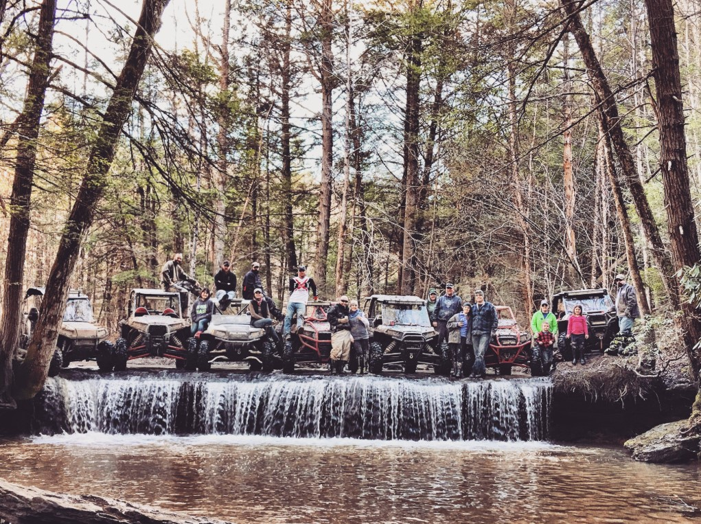 Several riders and their UTVs are posed at the top of a small waterfall in the forest of Brimstone.