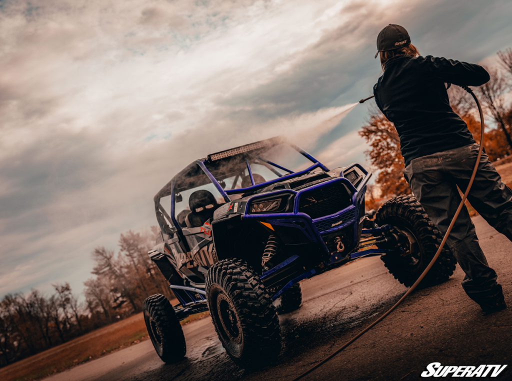 A woman spraying down a Polaris RZR Turbo 4. A clean vehicle will fetch a higher price.