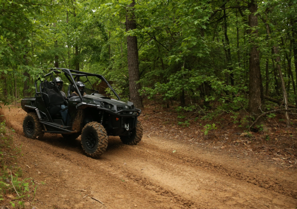 A black Can Am Commander on a dirt road