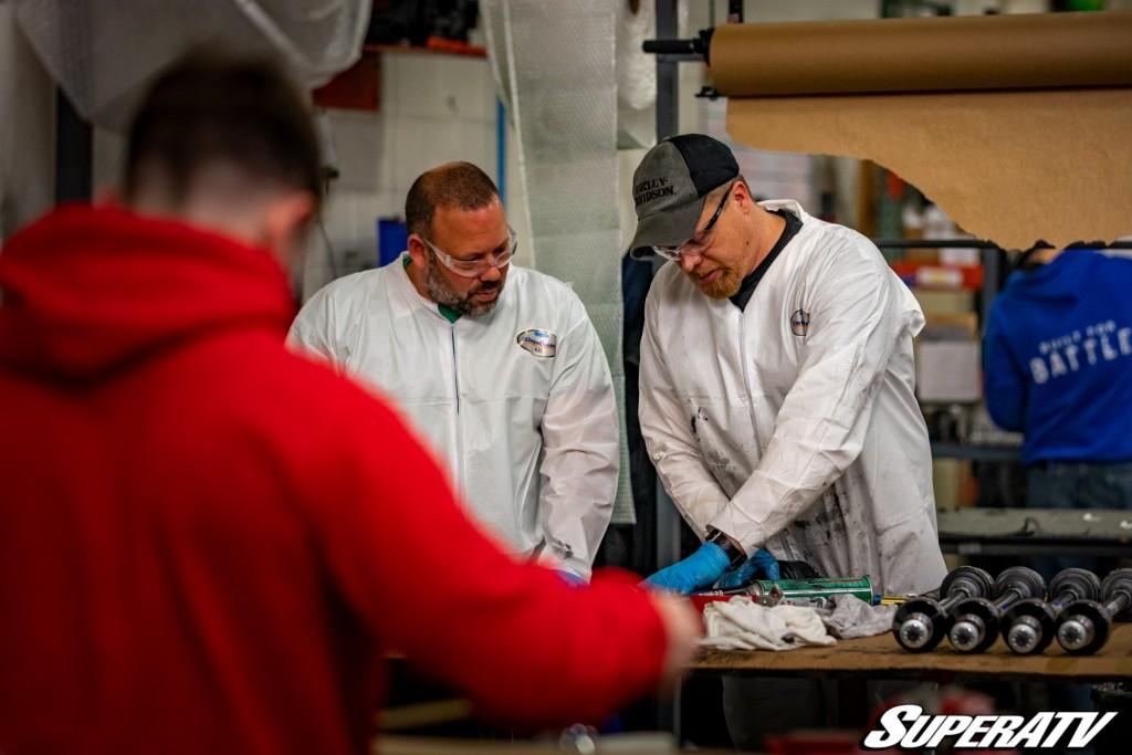 Craig Copeland works alongside another SuperATV employee inspecting Rhino brand axles.
