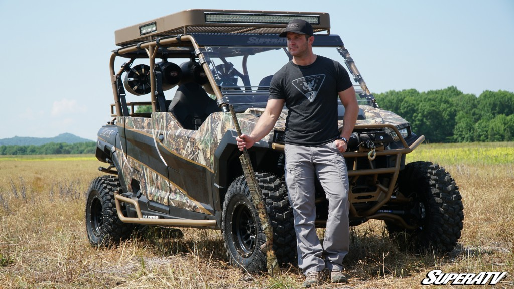 Easton Corbin stands in front of his custom SuperATV General build holding a hunting rifle. The rifle and the machine are wrapped in camo.