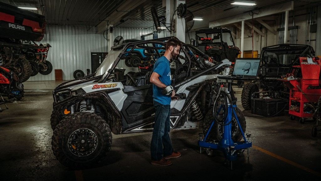 SuperATV employee Justin scans a RZR XP 1000 with the scanning arm to create an accurate 3D model for designing parts.