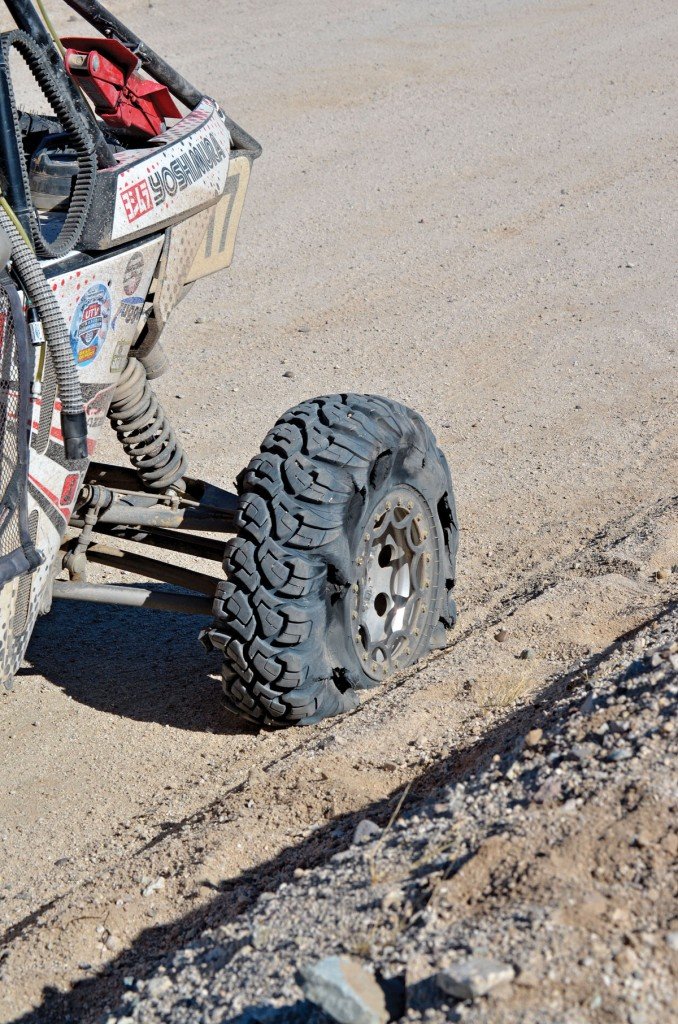 A close-up photo of a flat tire on a dirt trail