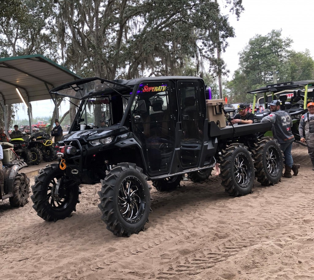 A photo of the King Boss Quad Can-Am Defender MAX 6x6 build, complete with a hydraulic 7' flat deck.