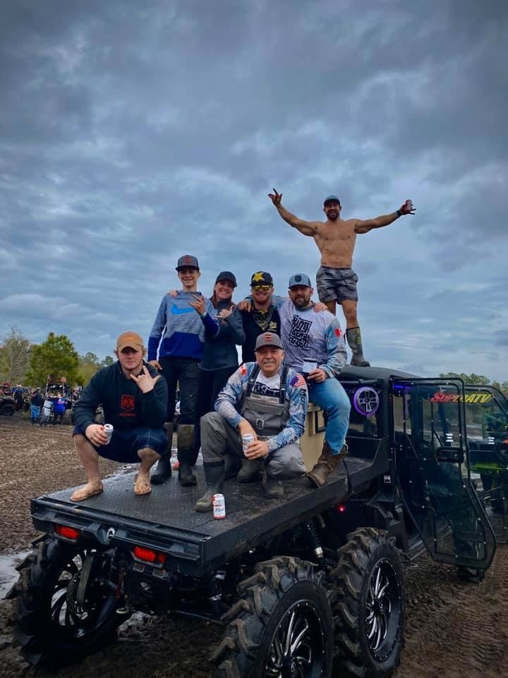 Nick and his team of friends and family pose on the custom deck of his Defender MAX 6x6 at Hog Waller Mud Bog in Florida.