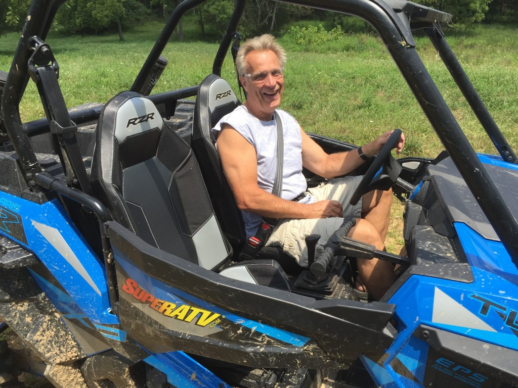 Harold in a blue RZR Turbo enjoying a sunny day ride.