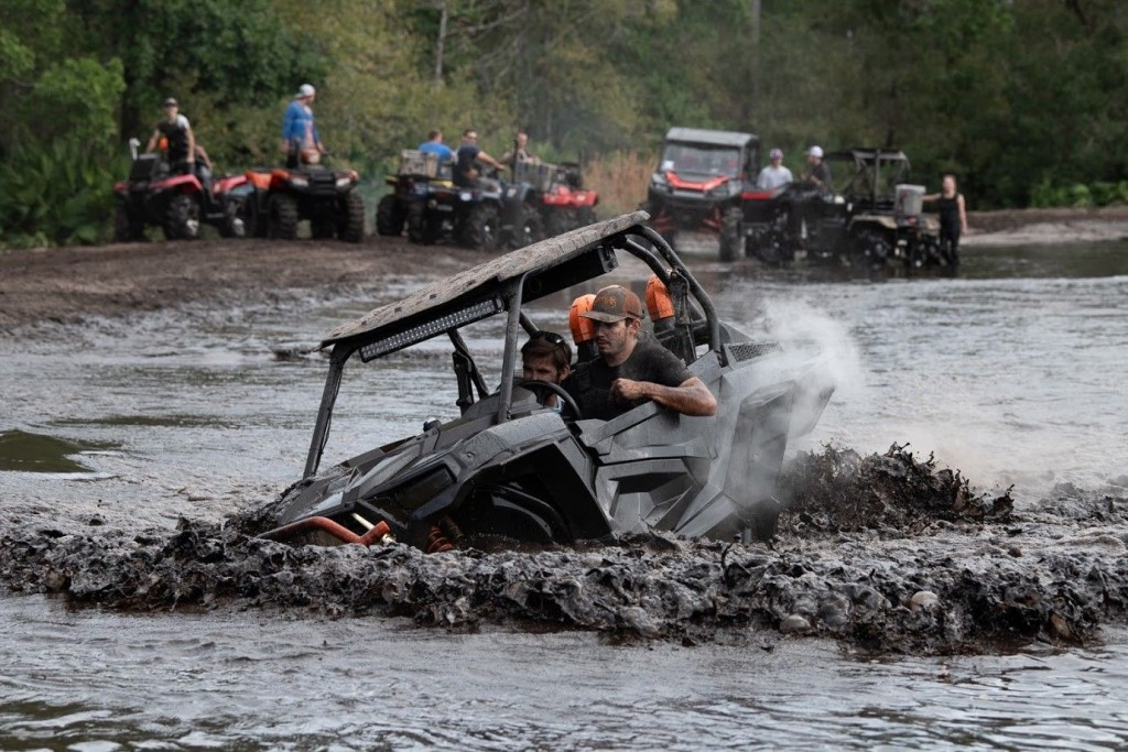 A man and his passenger cross the massive mud pit at Hog Waller Mud Bog & ATV in their side-by-side, while several other visitors look on.