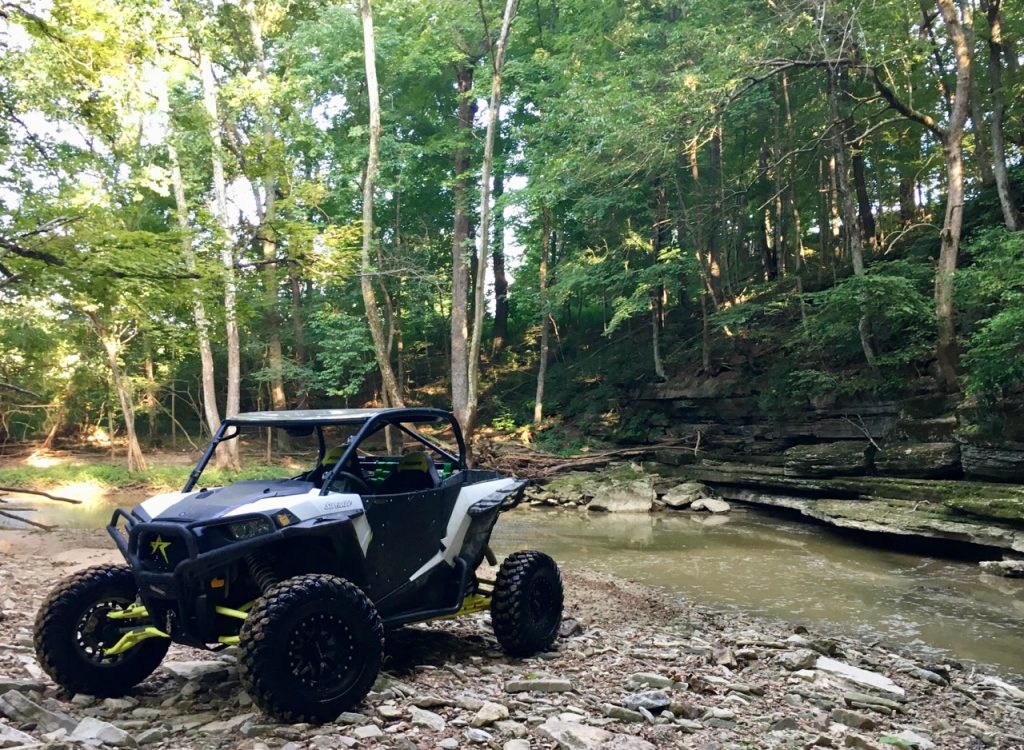 An upgraded RZR 1000 at a creek.