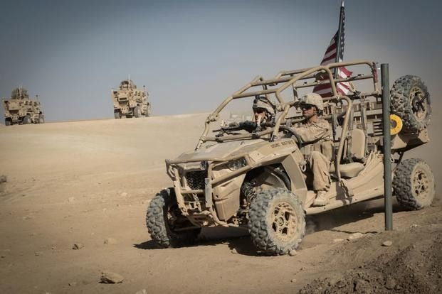 Two Marines ride a military UTV across the desert.