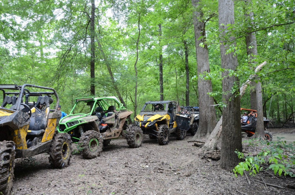 Several UTVs belonging to SuperATV team members are lined up on a trail at Muddy Bottoms.