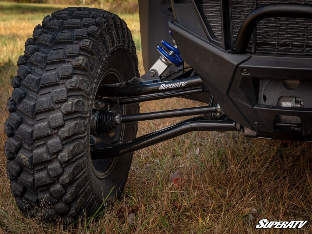 A close-up photo of SuperATV's A-arms installed on a machine