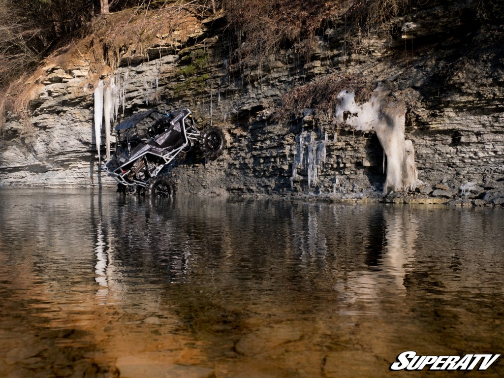 This photo shows our 2017 Polaris RZR Turbo mud build climbing a rock wall in a creek.