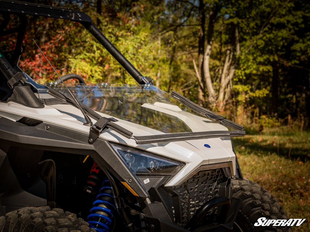 """A flip-down windshield is installed on a Polaris RZR PRO XP and set to the """"flip down"""" position (flat and secured against the hood)"""