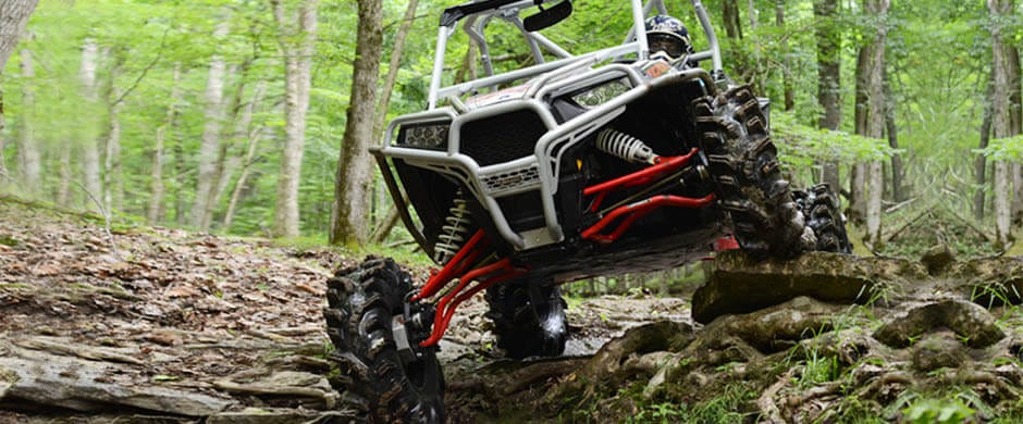 A polaris RZR creek riding with a set of SuperATV portals