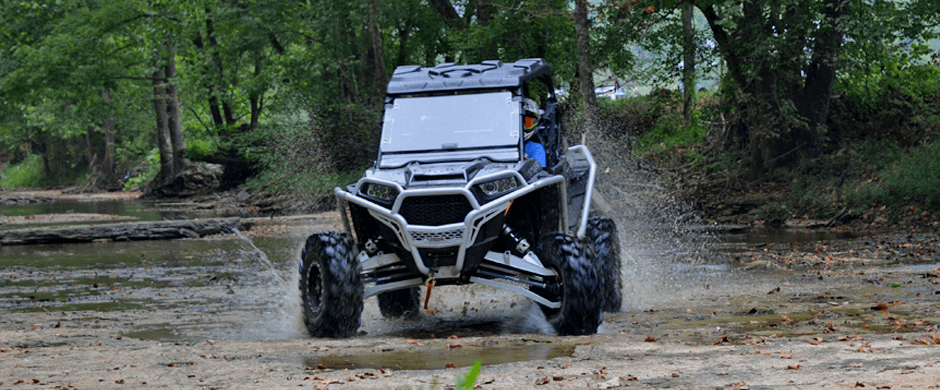 A RZR drifting in a creek bed