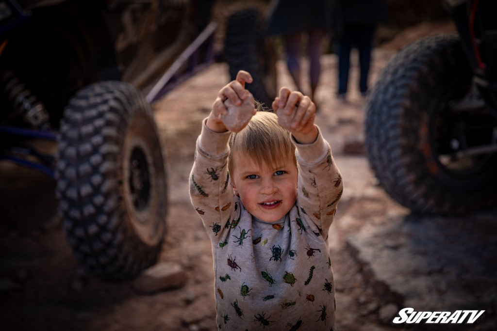 A photo of a small child with UTVs in the background