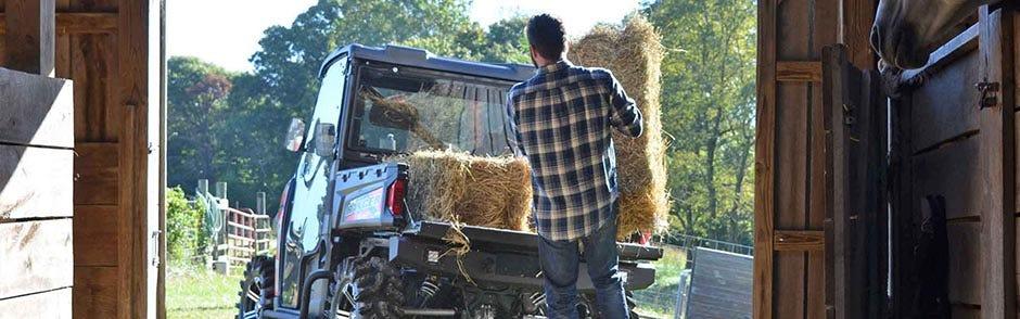 A rough-and-tumble farmer loading blocks of earth-hair in a Polaris Ranger