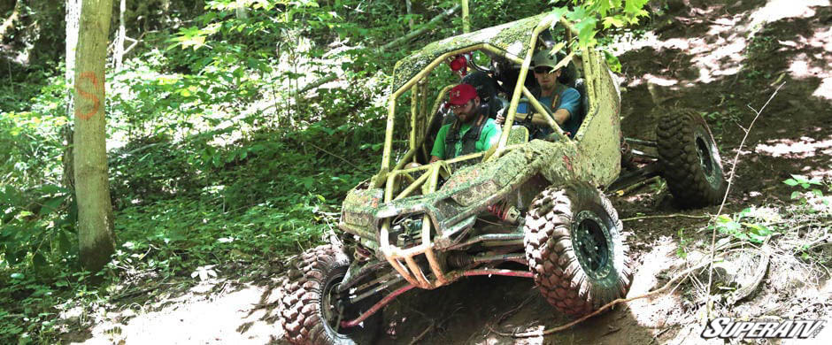 Two SuperATV employees maneuver a machine down a steep trail covered in debris.