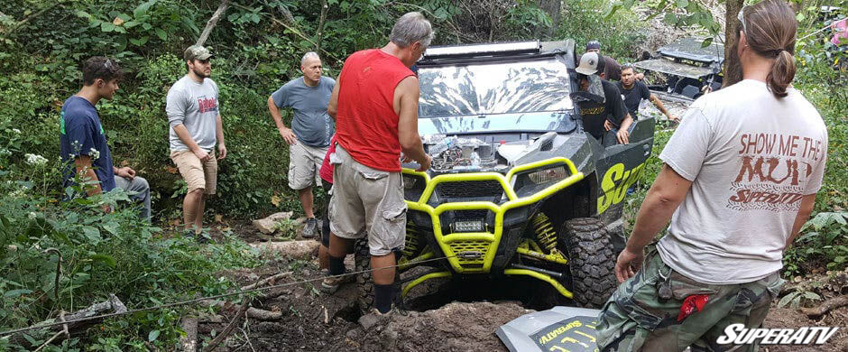 SuperATV employees look on while founder Harold Hunt gets a Polaris General back on the trail.