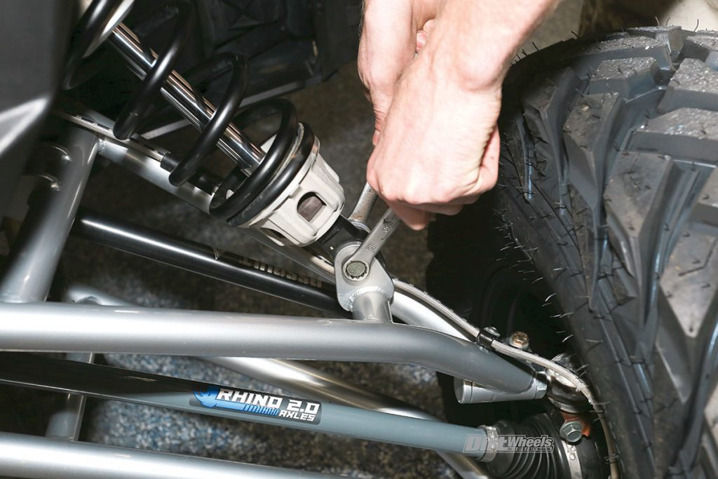 This close-up shot shows a rider tightening the bolts on his suspension.