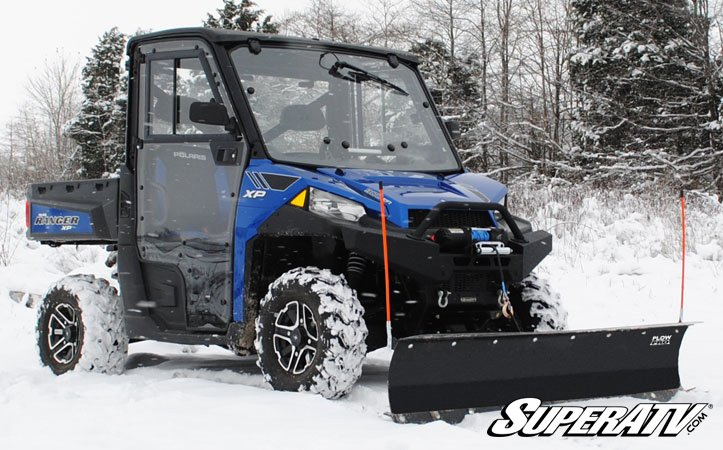 A UTV using a snow plow to clear a path.