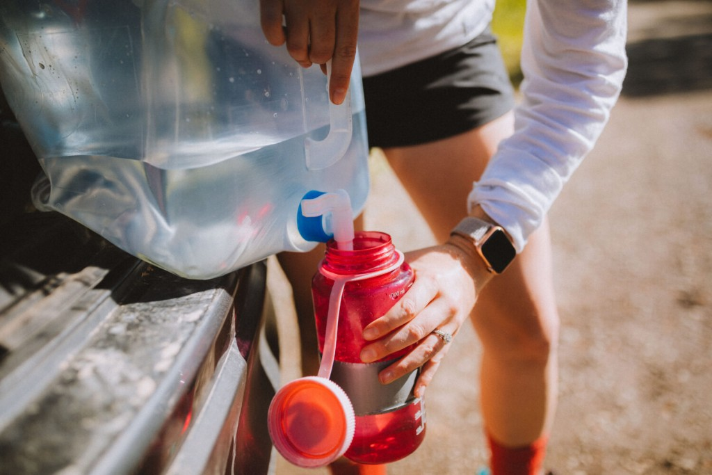 This photo shows someone filling up a reusable water bottle using a large jug. Never take off on a side-by-side adventure without plenty of H2O!