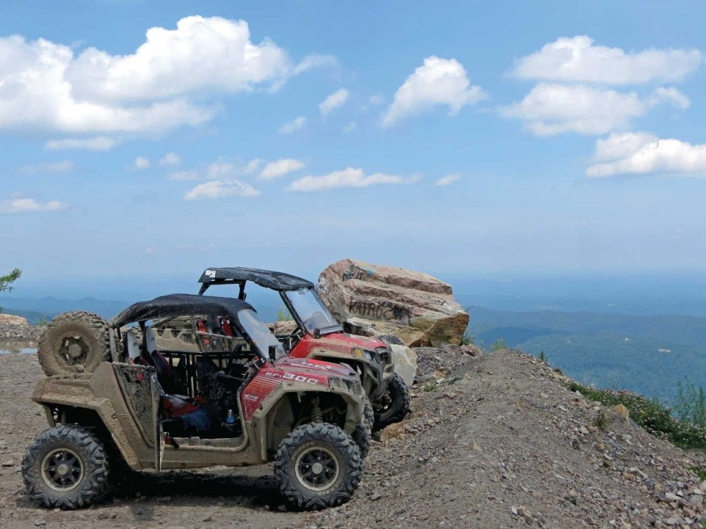 Two UTVs are parked at the top of a mountain with views of the Appalachian Mountains in the background.