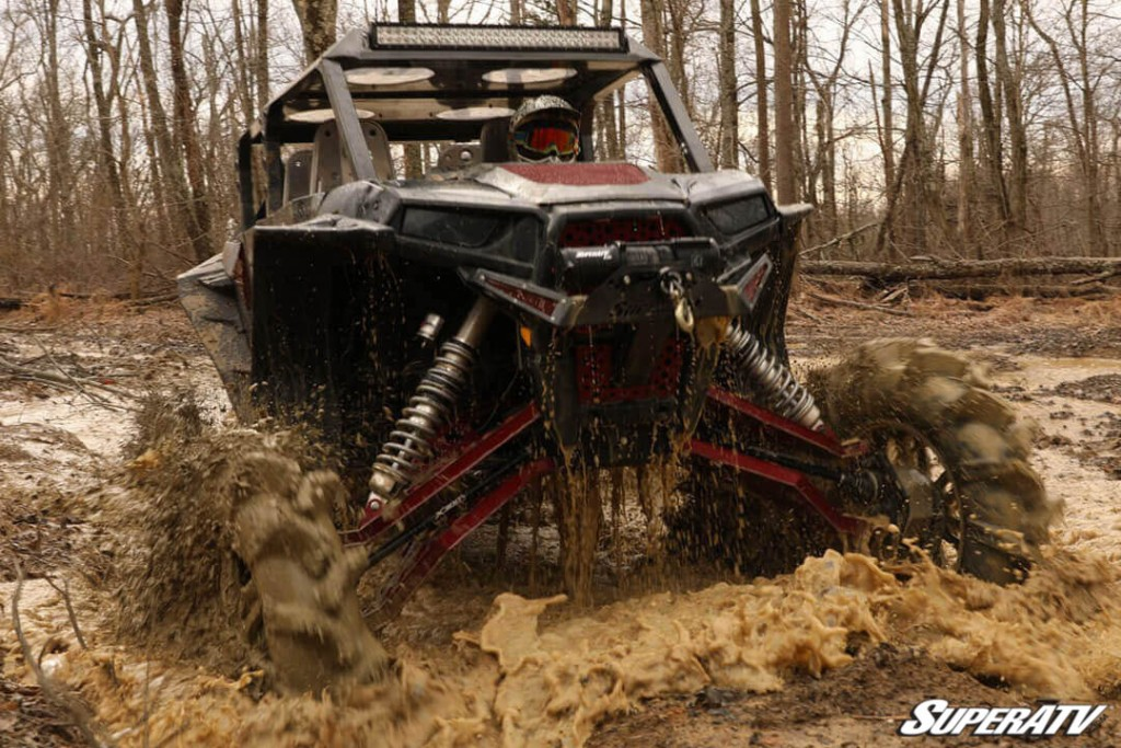 A machine equipped with SuperATV's X300 axles tears through mud and debris.