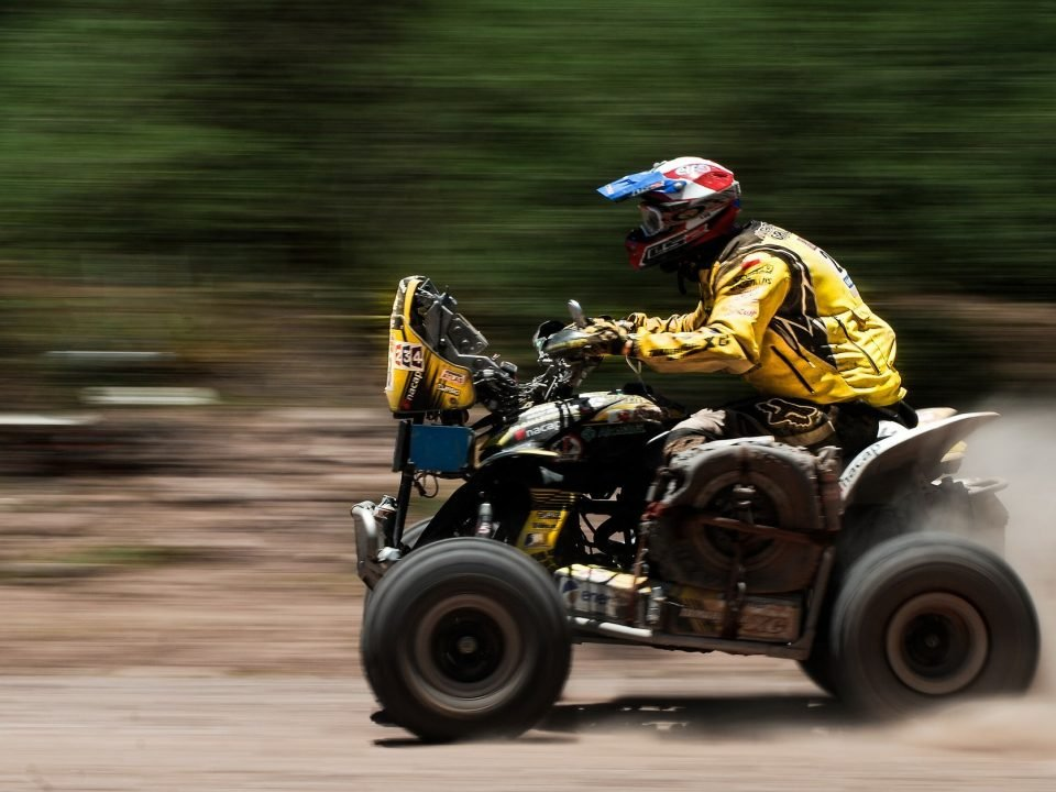 An ATV with a rider pushing it to its max speed.