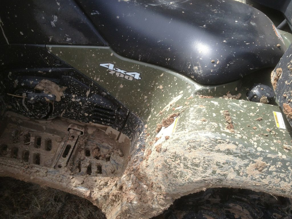 An ATV covered in mud with the 700cc decal visable.