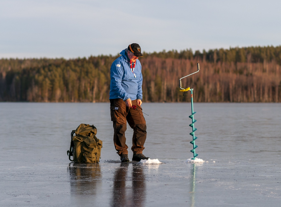 A person Ice fishing with a hand auger and gear