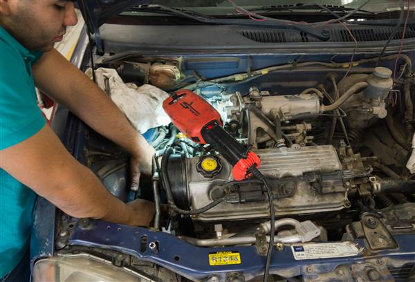 A student working under the hood of a vehicle