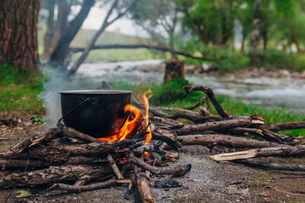 This picture shows a pot sitting on a campfire in the woods. This is the easiest and most obvious way to heat up your food on the trails, if needed.
