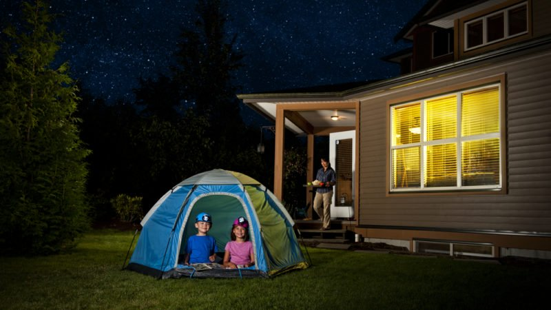 A family camps in a tent in the yard outside their home.