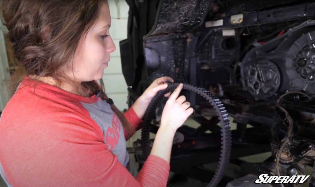 Kristen inspecting the drive belt for damage in a Maintenance Matters video.