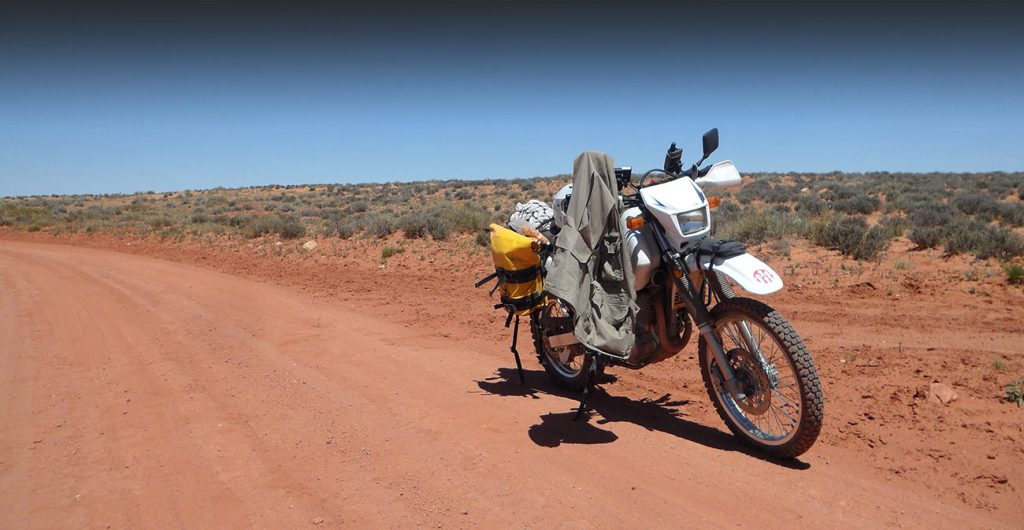 A motorcycle is parked in the desert in the middle of the TransAmerica Trail.
