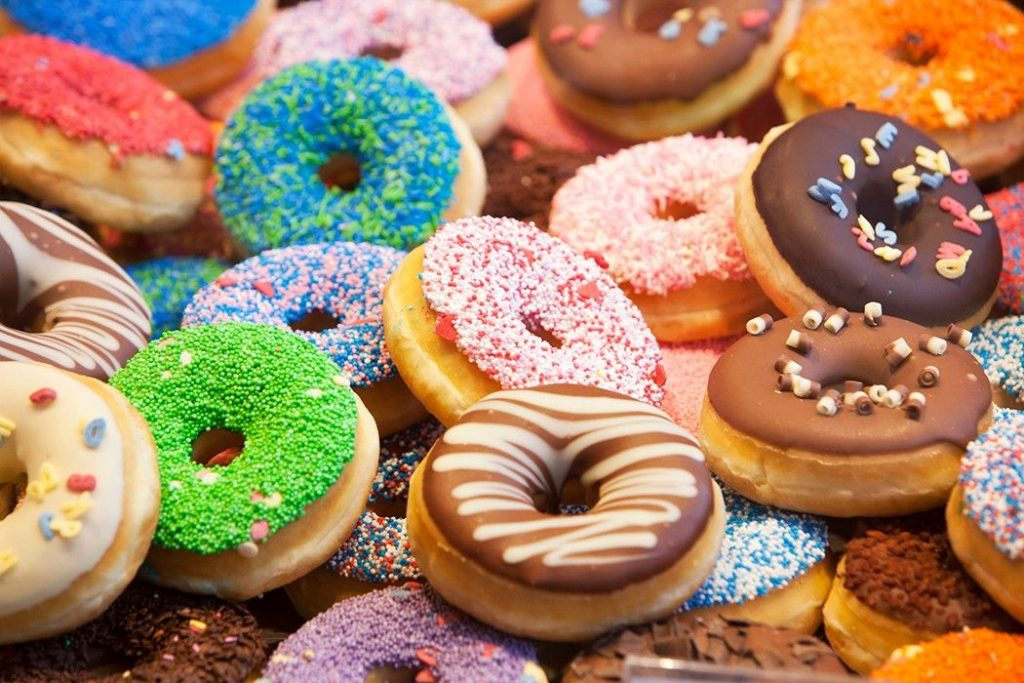 A close-up shot showing several colorfully decorated donuts
