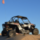 A RZR in the dunes with a 7-foot flag