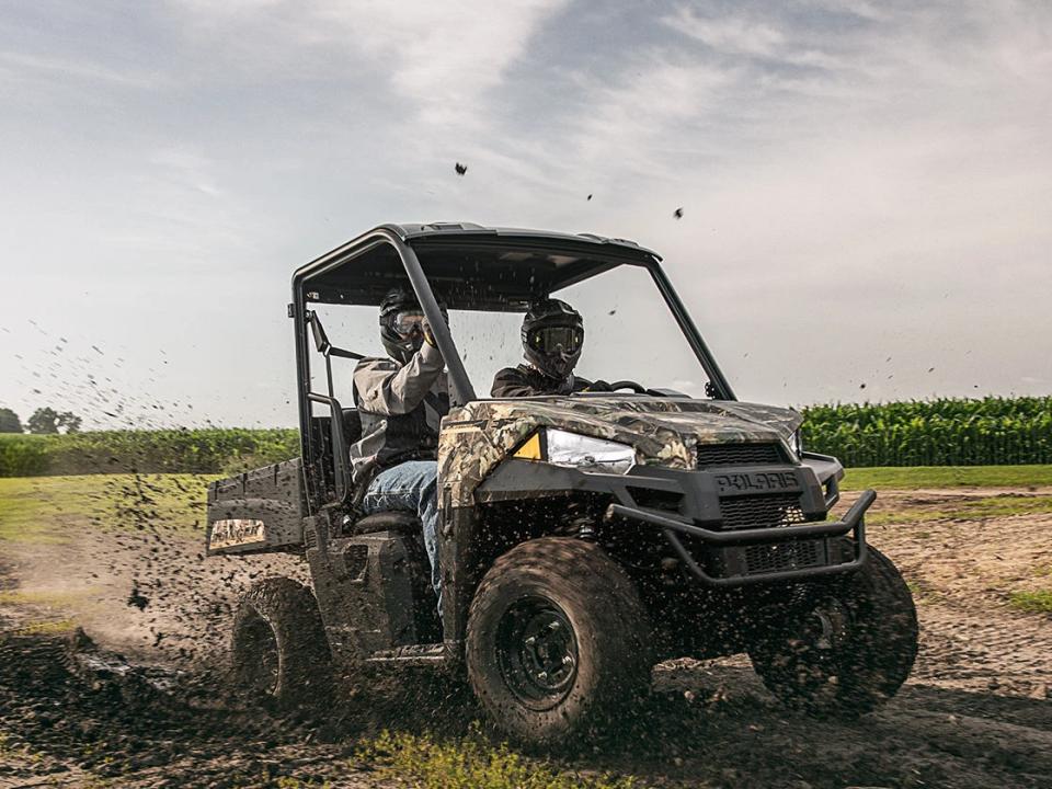 A Polaris Ranger EV Electric UTV riding through a muddy field
