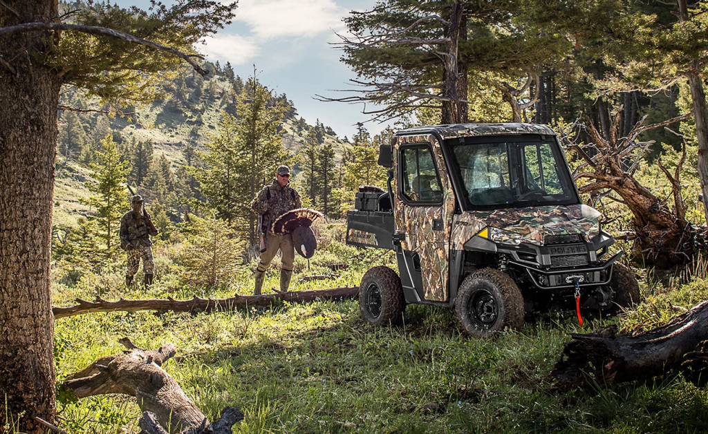 Two hunters brining in their wild turkey they caught thanks to the silent running of their Polaris Ranger EV electric UTV
