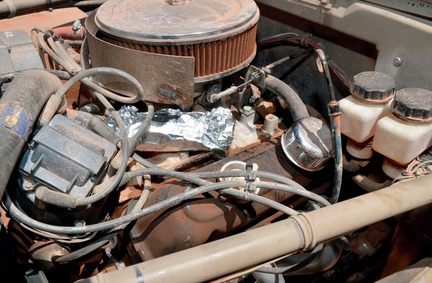 A burrito wrapped in aluminum foil cooks on top of a machine's engine.