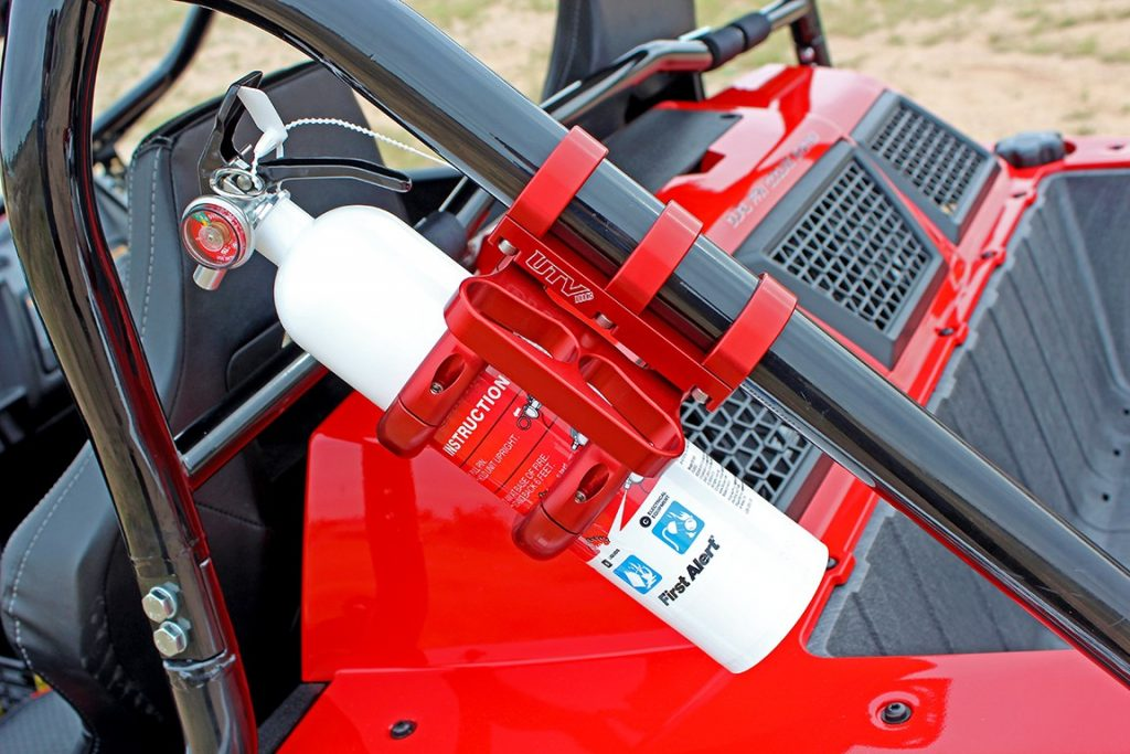 A fire extinguisher is secured to the frame of a UTV