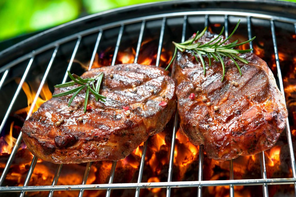 Two steaks are pictured on a charcoal grill.