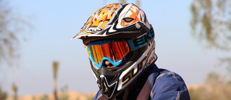 A rider models proper trail safety by sporting an orange and white helmet and blue reflective goggles.