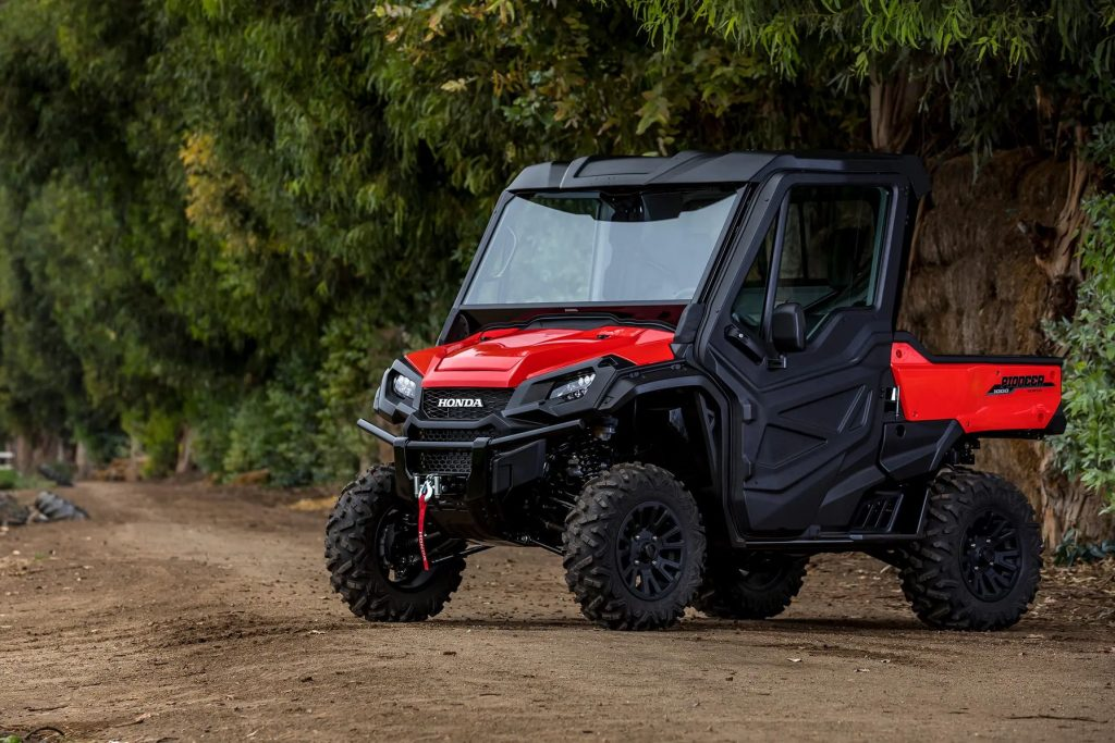 A red Honda Pioneer 1000 in the woods